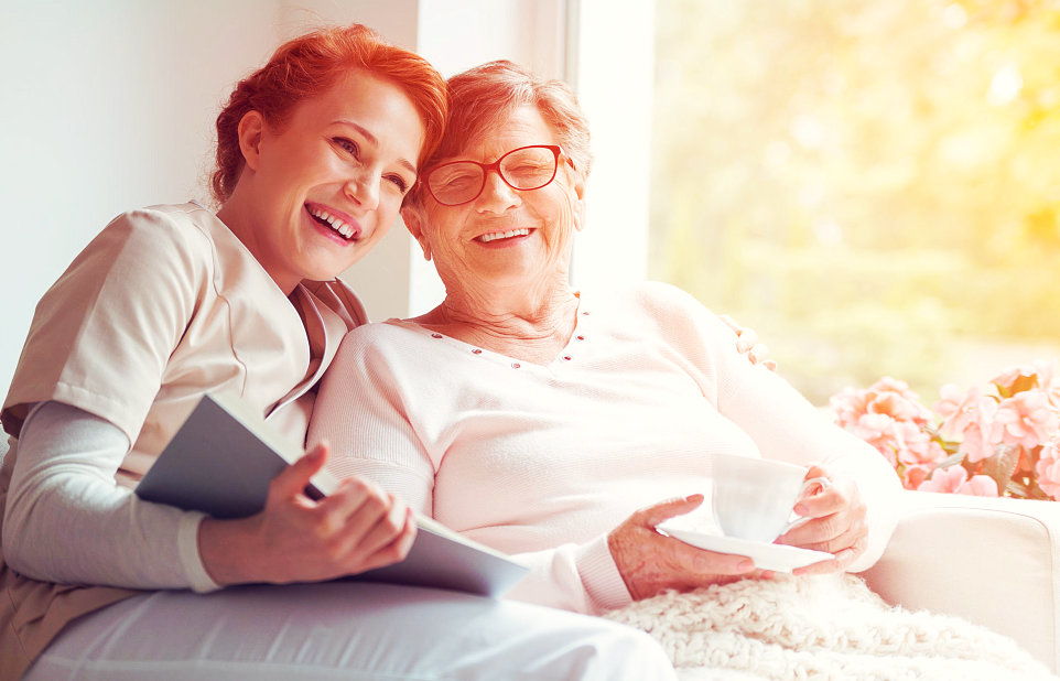 caregiver and senior woman wearing eyeglasses smiling
