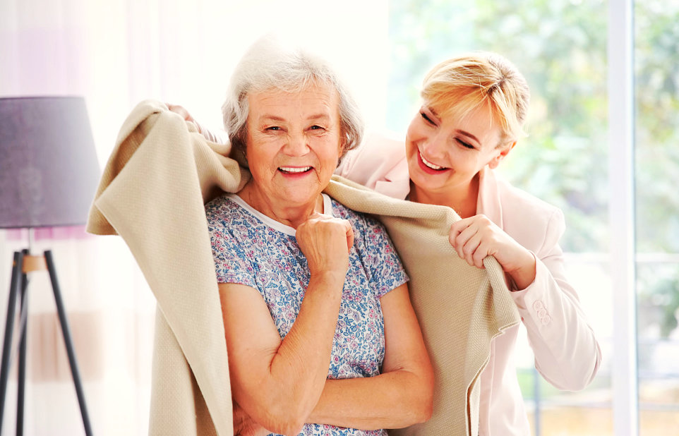 the adult woman puts a blanket on the back of senior woman smiling