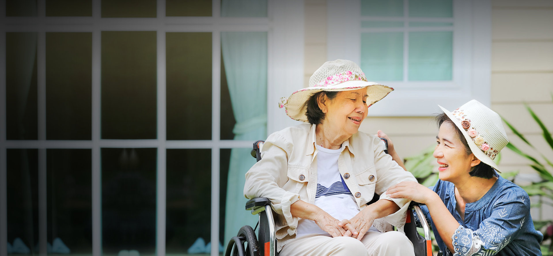 adult woman and senior woman sitting in the wheelchair smiling