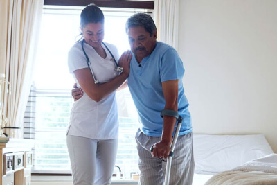female nurse assisting senior man in walking