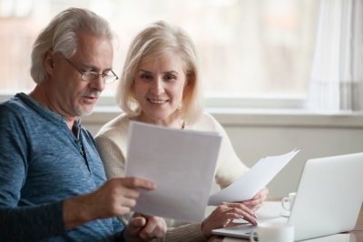 Happy old middle aged couple holding reading good news in document