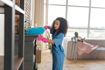 caring young medical attendant wearing pink gloves dusting the fireplace in the living room
