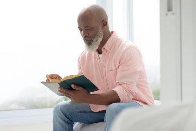 man reading a book and sitting on the bed in the bedroom