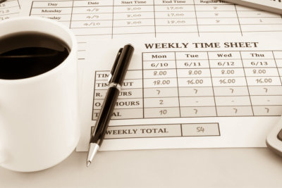 time sheets place on office table with cup of coffee