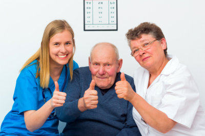 elderly showing thumbs up with their caregiver