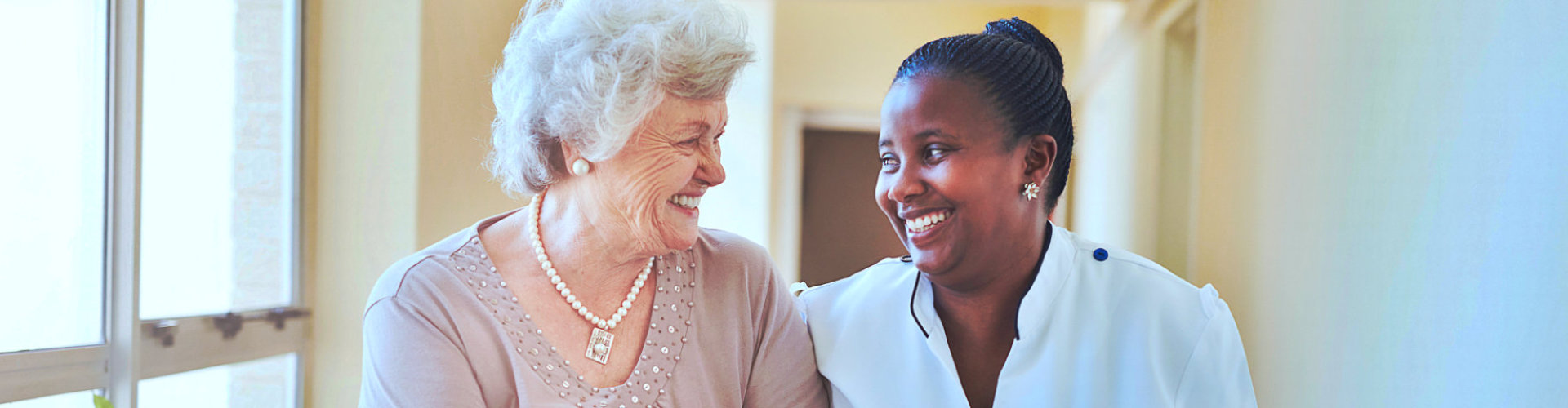 senior woman and nurse smiling